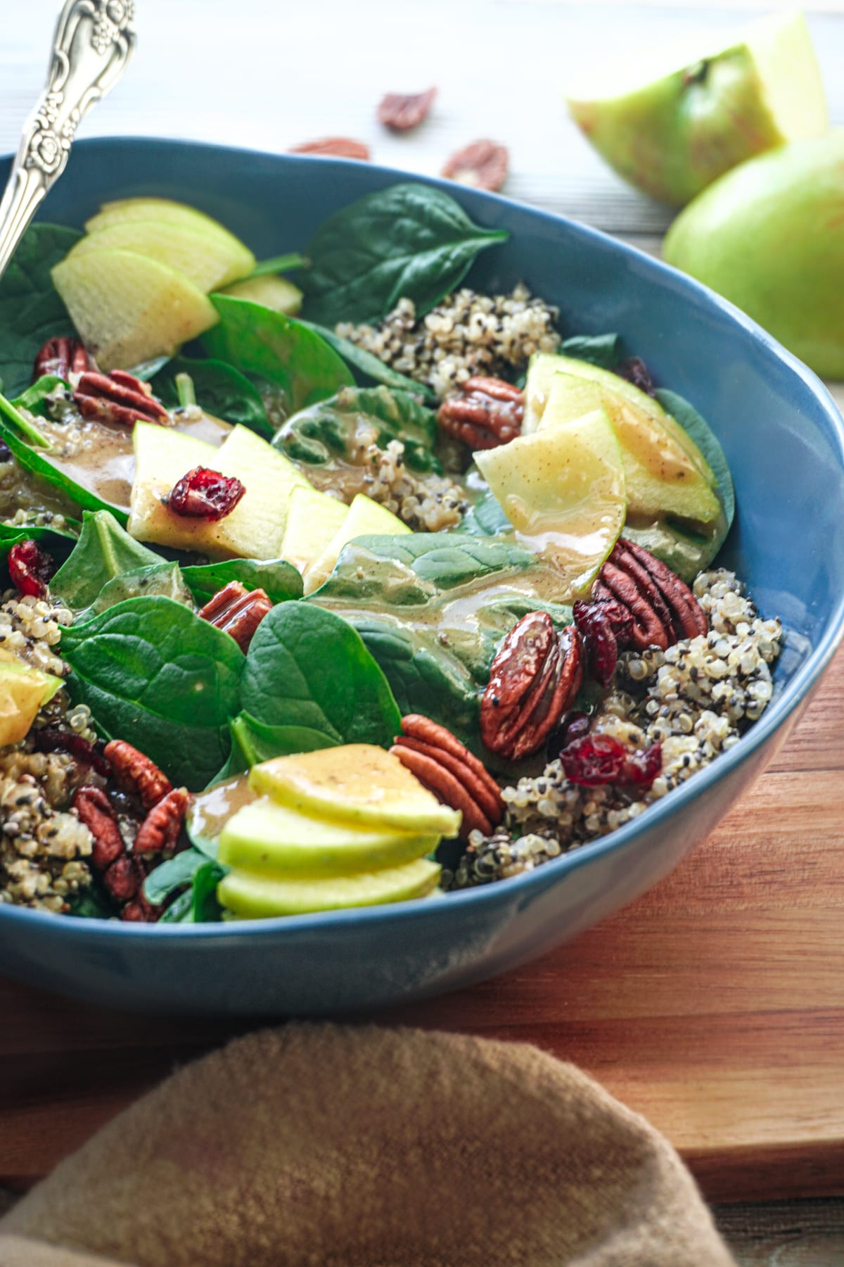 a big blue bowl of vegan fall salad with apples and pecans.