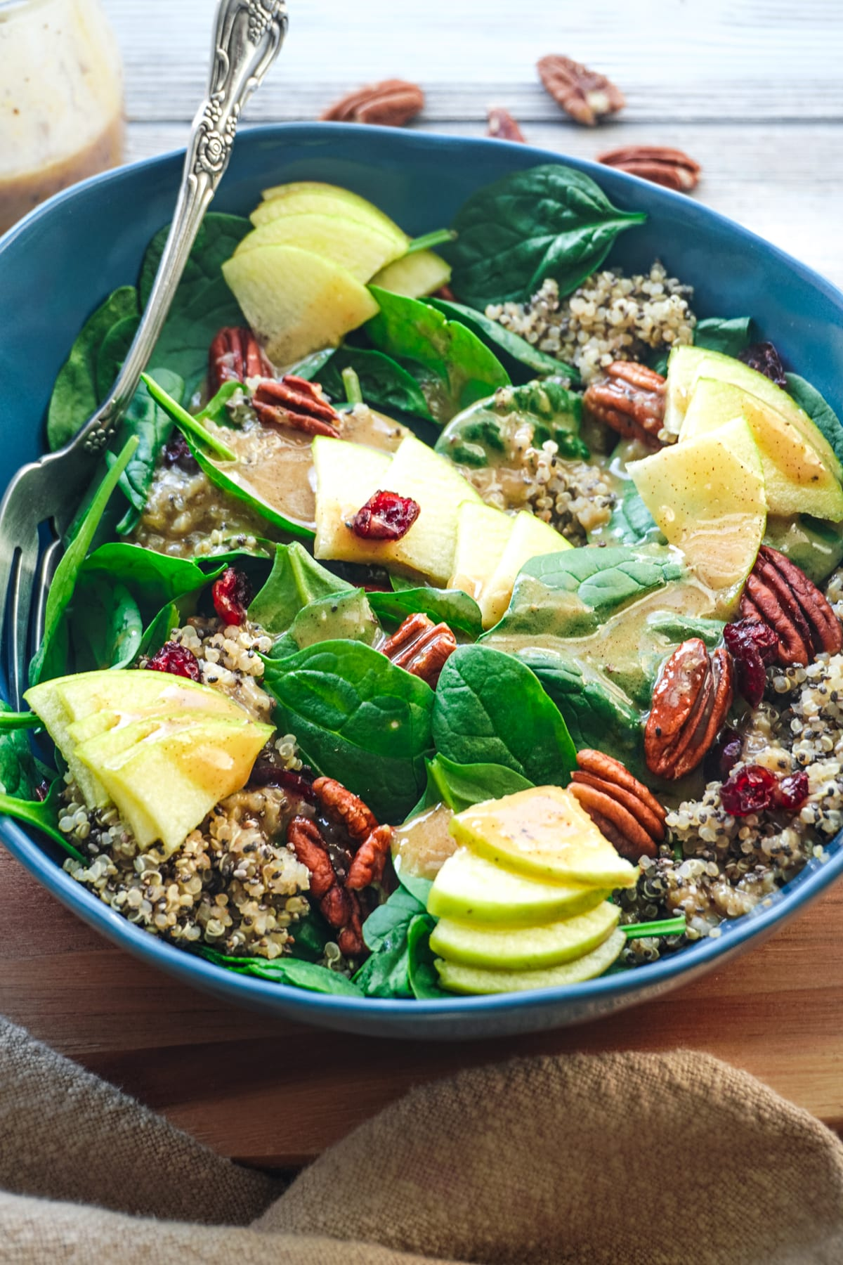 A big blue bowl of fall-inspired salad with a warm nutty dressing