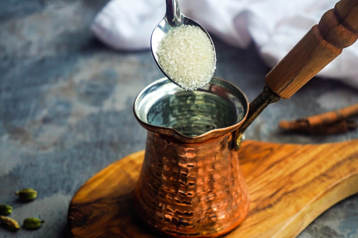 a traditional Turkish coffee pot and a spoonful of sugar
